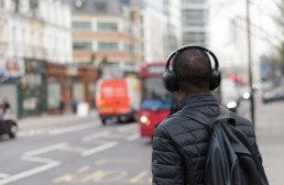 man standing on a street wit headphones on