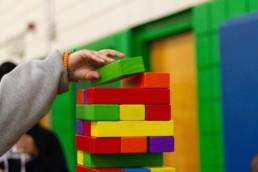 Kid Building a Big Colorful Jenga Tower